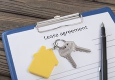 Form of the lease agreement, two keys from the front door. On a key fob in the form of a house on the background of a wooden table. business. Sew housing. the Stock Photo