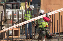 Form Raising. Workmen assembling a large form for a concrete wall stock photo