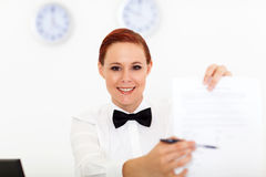 Form for signing. Friendly hotel receptionist giving form for signing Stock Photos
