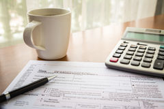 Form 1040A, U.S. Individual income tax return. Place on table with a cup of coffee, calculator and pen stock photo