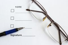 Form for voting and signing near the pen, glasses stock photography