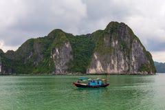 Formação de rocha com o barco de pesca azul tradicional, herança natural da baía de Halong do mundo do UNESCO, Vietname imagens de stock royalty free