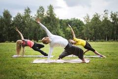 Formação no parque - o instrutor mostra o exercício da flexibilidade para o grupo de meninas no parque Imagem de Stock Royalty Free