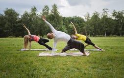 Formação no parque - o instrutor mostra o exercício da flexibilidade para o grupo de meninas no parque Foto de Stock