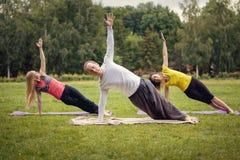 Formação no parque - o instrutor mostra o exercício da flexibilidade para o grupo de meninas no parque Fotos de Stock