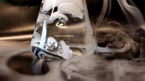 Formação pesada do fumo do movimento lento de dióxido de carbono na água da pelota de gelo seco com vista próxima filme