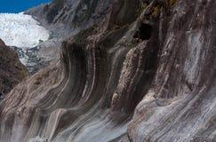 Formações de rocha estranhas no primeiro plano e no Franz Josef Glacier no fundo no Mt Cozinhe/parque nacional de Aoraki dentro imagem de stock royalty free