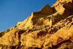 Formações naturais do arenito: formado das grões de areia cimentadas, amarelo-alaranjadas na cor, formando penhascos ásperos cont imagens de stock