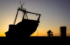 Forma av ett fartyg på jordningen i en härlig solnedgång royaltyfria foton