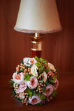 Forma clássica do ramalhete do casamento, com as rosas de creme e cor-de-rosa da peônia, bagas no nightstand ao lado da lâmpada Fotografia de Stock