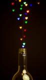 A forma colorida do coração ilumina a flutuação fora da garrafa Foto de Stock