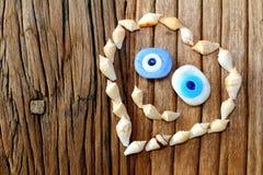 Forma creativa del corazón con la cáscara del mar y del amuleto que sonríe en un backround de madera de la tabla Fotografía de archivo libre de regalías
