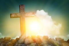Forma cruzada de madera en la colina rocosa en la puesta del sol con el cielo azul fotos de archivo
