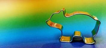 Forma d'argento metallica per i biscotti ed i biscotti sotto forma di orso polare con un fondo dell'arcobaleno immagine stock libera da diritti