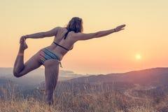 Forma d'esecuzione castana attraente di yoga al tramonto fotografia stock libera da diritti