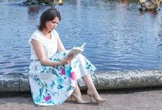 A forma da mulher consideravelmente nova agradável do moderno está sentando-se na grama verde em uma blusa e em uma saia longa Fotografia de Stock Royalty Free