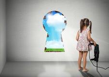 Forma da parede da ruptura da menina da criança do buraco da fechadura, conce criativo da cognição fotografia de stock royalty free