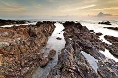 Forma da rocha na praia durante o nascer do sol, Terengganu de Pandak, Malásia Fotos de Stock Royalty Free