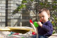 Forma da tomada do menino do bebê de um ano da areia na caixa de areia no jardim em um dia de mola ensolarado Imagem de Stock