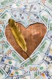 Forma de bronce de cobre del corazón y pluma de canilla del oro en el centro del dinero imagen de archivo