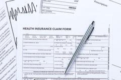 Forma de demanda del seguro médico con la pluma de plata foto de archivo libre de regalías