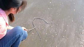 Forma de dibujo del corazón de la muchacha en la playa