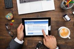 Forma de Filling Online Survey del hombre de negocios Imagen de archivo libre de regalías