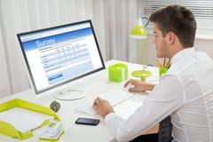 Forma de Filling Online Survey del hombre de negocios en el ordenador Imagen de archivo