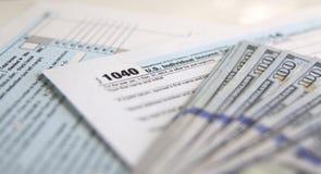 Forma de impuesto 1040 con 100 dólares Imagenes de archivo