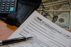 Forma de impuesto 1040, dólares, cartera, pluma, calculadora en una tabla de madera fotos de archivo