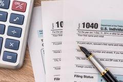 forma de impuesto del año 1040 con la calculadora y la pluma Foto de archivo