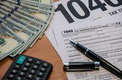 Forma de impuesto 1040, pluma, dólares, calculadora en la tabla fotos de archivo