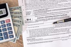 Forma de impuesto W4 con el dinero y la pluma fotos de archivo
