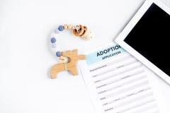 Forma de la adopción con la tableta en concepto de familia en maqueta de la opinión de sobremesa Foto de archivo