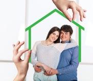 Forma de la casa verde con la familia joven dentro Fotografía de archivo libre de regalías