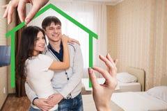 Forma de la casa verde con la familia joven dentro Fotografía de archivo