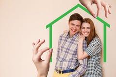 Forma de la casa verde con la familia joven dentro Imagen de archivo