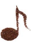 Forma de la nota musical hecha de los granos de café sobre el fondo blanco Foto de archivo