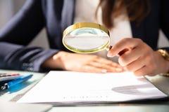 Forma de Looking At Contract de la empresaria a trav?s de la lupa fotos de archivo libres de regalías