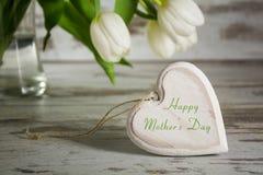 Forma de madera del corazón delante de los tulipanes blancos en una etiqueta rústica gris Imagen de archivo libre de regalías