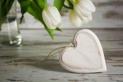 Forma de madera del corazón delante de los tulipanes blancos en una etiqueta rústica gris Imagenes de archivo