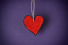 Forma de papel vermelha do coração contra o fundo roxo foto de stock royalty free