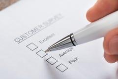 Forma de Person Hands Filling Customer Survey Fotografía de archivo libre de regalías