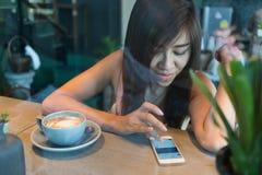 Forma de vida de las mujeres usando un teléfono móvil en café del café Imágenes de archivo libres de regalías