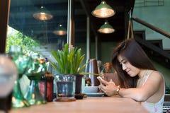 Forma de vida de las mujeres usando un teléfono móvil en café del café Foto de archivo libre de regalías