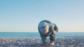 Forma de vida del bebé Juegan a un muchacho con la arena y las piedras en una playa natural Tirado con el stedicam almacen de video