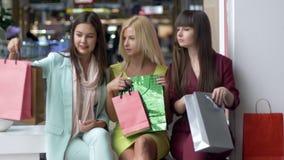 Forma de vida del comprador, muchachas con muchos bolsos que discuten su día de las compras que se sienta en alameda durante vier metrajes