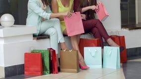 Forma de vida del comprador, muchachas que consideran hacer compras en las bolsas de papel cerca de las piernas después de visita almacen de metraje de vídeo