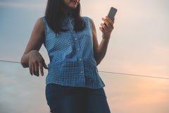 Forma de vida del concepto moderno de la gente Mujer joven relajante por datos o el mensaje de lectura vía Smartphone El mantener fotos de archivo libres de regalías