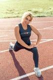 Forma de vida deportiva Mujer joven en el paso del estadio adelante que estira las piernas en la sonrisa de la pista alegre fotografía de archivo